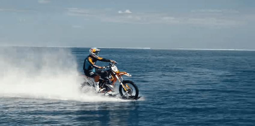 Watch: man surfs with dirt bike, rides across ocean